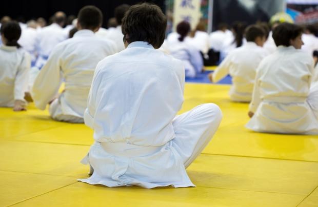 People in kimono warming up on tatami on martial arts training seminar