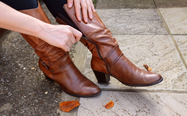 Woman zips up high-heeled tan leather boots, autumn leaves scattered at her feet