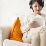 Woman is reading a magazine while listening to music