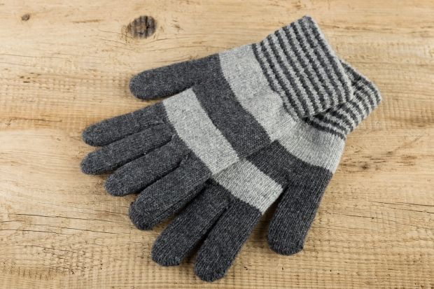Knitted gloves on wooden background