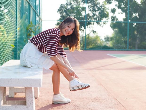 portrait of beautiful sport girl sitting in tennis courts  looking to camera with smiling face use for people and healthy lifestyle activities