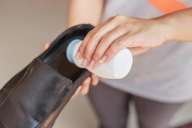 Close up Hand put powder to a shoe, odor stop