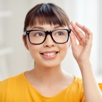 people, education, vision and portrait concept - happy asian young woman or teenage student girl in glasses at home