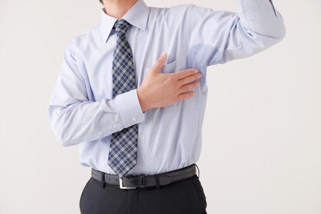 汗じみのシャツを触る男性
